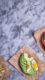 Beautiful healthy snack - sandwiches with rye bread with avocado and egg, mozzarella
