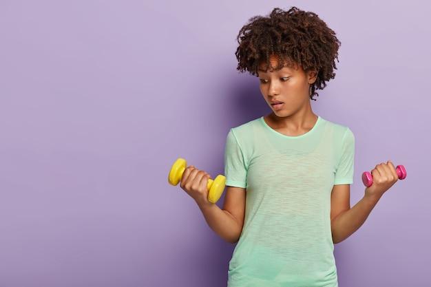 La bella sportiva in buona salute solleva piccoli manubri, ha uno sguardo sorpreso