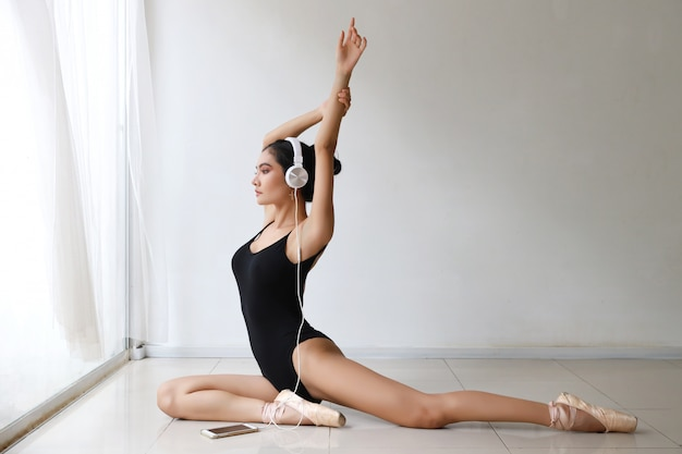 Beautiful healthy and sporty asian young woman in black sportswear with headphone, listening music from mobile phone while training ballet dancing