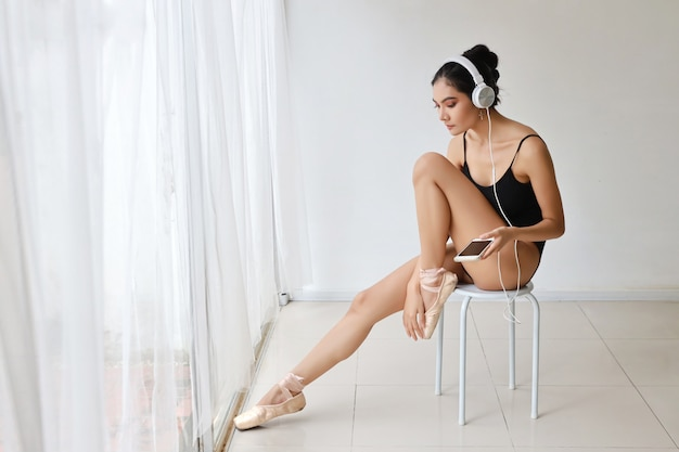 Beautiful healthy and sporty asian young woman in black sportswear with headphone, using cell phone while practicing ballet