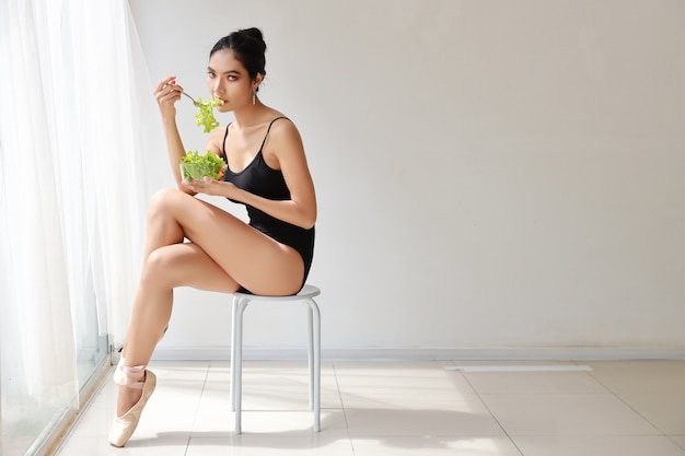 Beautiful healthy and sporty asian young woman holding salad bowl and eat after training