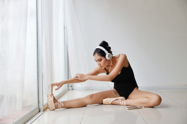 Beautiful healthy and sporty young asian woman in black sportswear sitting with headphone, listening music from mobile phone while training ballet dancing on white wall .technology and healthy concept