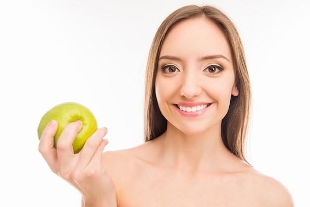 青リンゴと笑顔の美しい健康な歯を見せる女の子