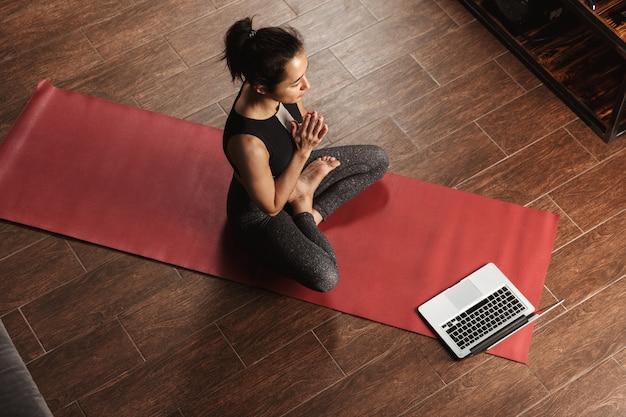 Красивая здоровая женщина делает упражнения йоги, сидя на фитнес-коврике дома, используя портативный компьютер, растягивая