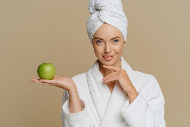 Beautiful healthy woman touches chin gently holds green apple has perfect smooth skin