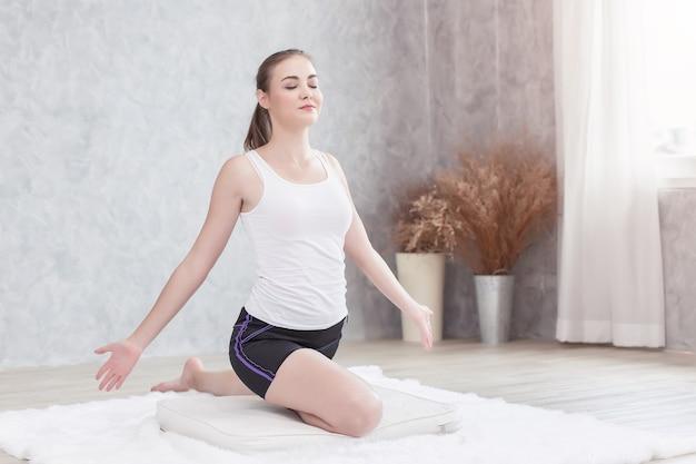 目を閉じてヨガをしている美しい健康な女性は、集中瞑想の姿勢をリラックスしてリラックスします