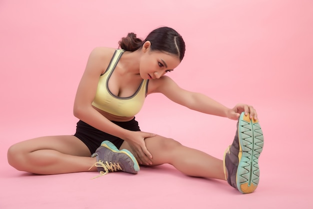 Beautiful healthy young asian woman doing a stretching exercise before playing a sport.