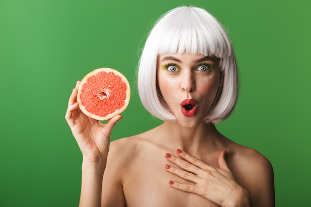 Красивая здоровая молодая женщина топлес в коротких белых волосах стоит изолированно, показывая нарезанный грейпфрут