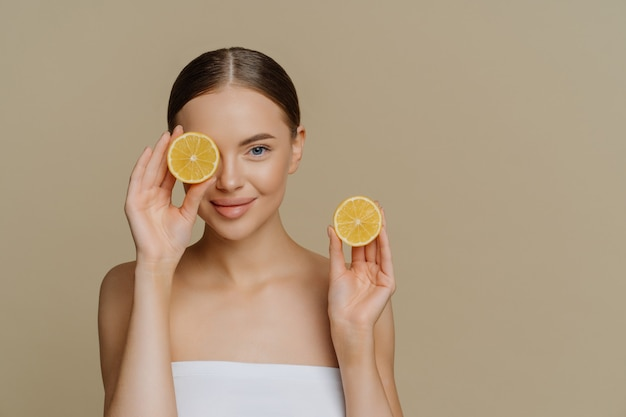 Beautiful healthy young woman covers eye with half of lemon enjoys spa treatment wrapped in bath towel