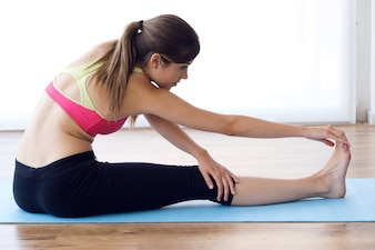 Beautiful healthy young woman doing exercise at home.