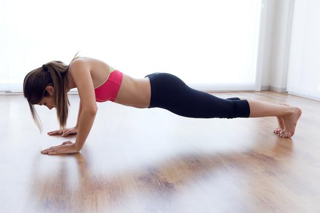 Bella giovane donna sana fare esercizio a casa.