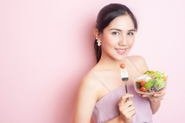 Beautiful healthy young woman eating salad on pink background
