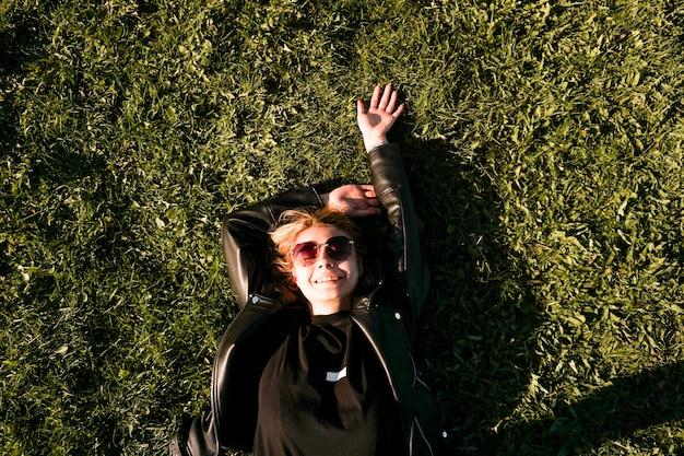 Красивая здоровая молодая женщина, лежа и расслабляясь на зеленой траве