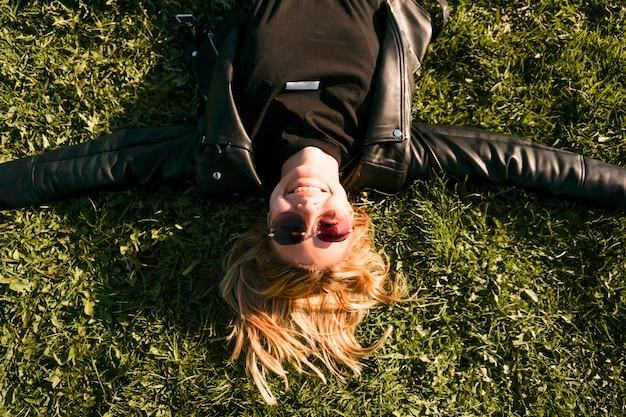 Beautiful healthy young woman lying and relaxing on the green grass