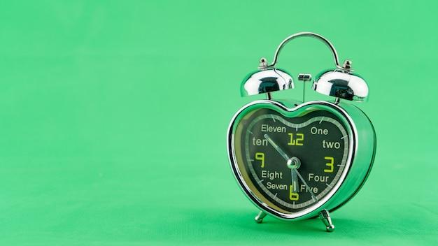 녹색 화면 배경에 아름 다운 마음 알람 시계 아침 시간에 알람 시계 얼굴 최소한의 알람 시계 개념 시간대입니다.
