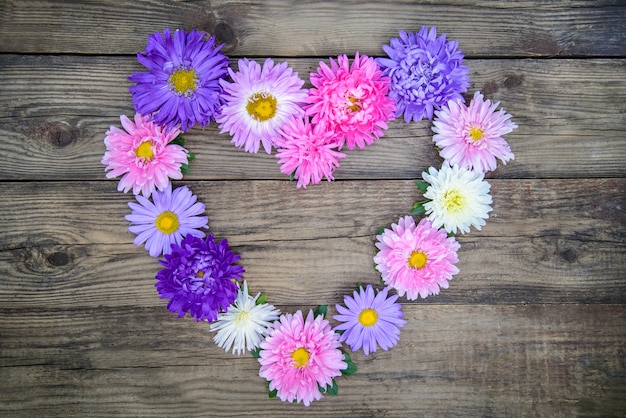 Beautiful heart of colorful flowers on a wooden table, top view