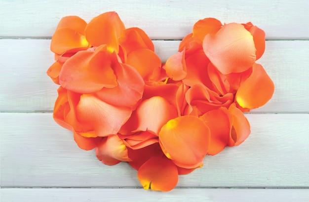 木製のテーブルにバラの花びらの美しい心