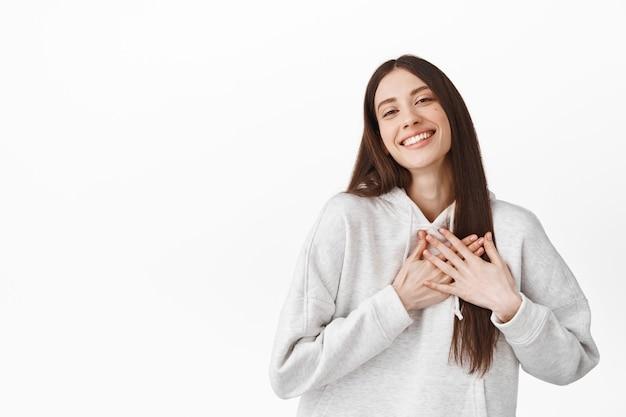 心に手をつないで、感謝の気持ちを浮かべて、気持ちの良い素敵なジェスチャーに触れ、感謝の気持ちを表し、ありがとう、白い壁の上に立っている美しい心のこもった女の子