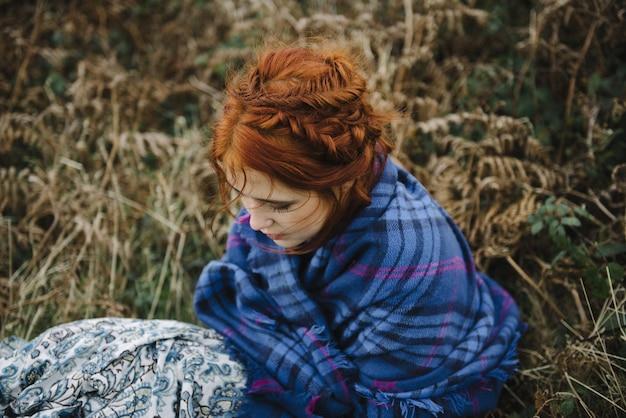青いカバーで真っ白な肌を持つ生姜の女性の美しいハイアングルショット