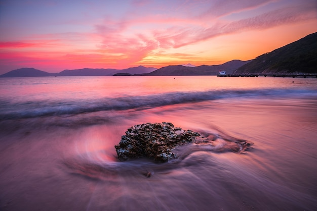 Beautiful high angle shot of a rock in a wavy sea under an orange and pink sky at sunset
