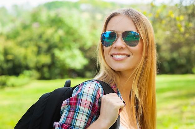 美しいハイカー。彼女のバックパックを運び、自然の中で立っている間肩越しに見ているサングラスの美しい若い女性