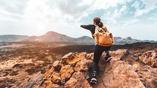 サンセットバレーを指している山の頂上に美しいハイカーの女性。バックパックを持った少女は自然の中で一人旅をします。
