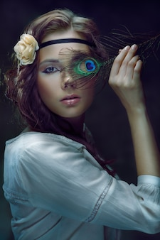 孔雀の羽で片目を覆う美しいヒッピーの女の子
