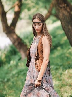 春の森の背景に美しいヒッピーの女の子