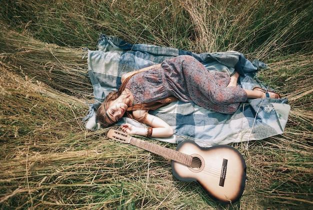 깎은 잔디에 기타가 누워 있는 아름다운 히피 소녀