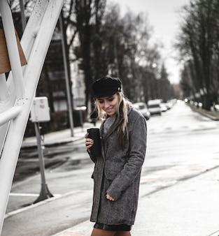 一杯のコーヒーを手で押し、屋外に立っている間よそ見スタイリッシュなコートで美しい内気な少女。コーヒーを飲む若いおしゃれな女性。アーバンファッションのコンセプト