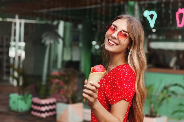 Beautiful hipster girl in sunglasses eating ice cream and smiling