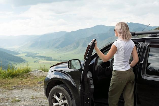 선글라스의 아름다운 힙 스터 여자는 자동차로 여행하고 산의 경치를 즐기고 휴가에 차를 빌려줍니다.