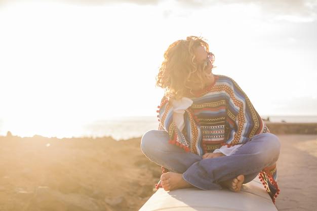 コンクリートの堤防に座って、背景に海の景色を眺めながら美しい流行に敏感な女性。海沿いのフェンスで囲まれた壁でリラックスして休日を楽しんでいる女性のシルエット