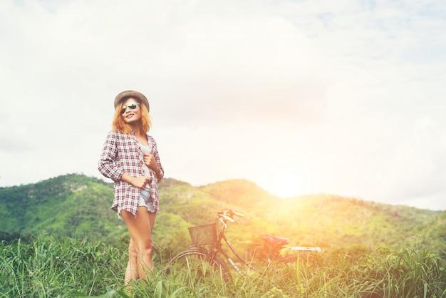 自然のaと緑の草原の上に立って、美しいヒップスターの女性