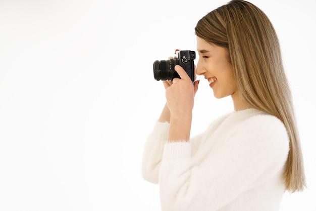 흰색 바탕에 검은 복고풍 필름 카메라로 사진을 찍고 아름 다운 hipster 여자. 확대. 실내. 따뜻한 색. blogger