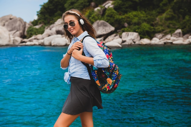 Beautiful hipster woman traveling around world with backpack, smiling, happy, positive, listening music in headphones, blue tropical ocean background, sunglasses, sexy, summer vacation,
