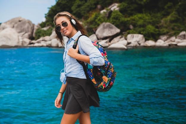 バックパック、笑顔、幸せ、ポジティブ、ヘッドフォンで音楽を聴く、青い熱帯の海の背景、サングラス、セクシー、夏休み、世界中を旅する美しい流行に敏感な女性