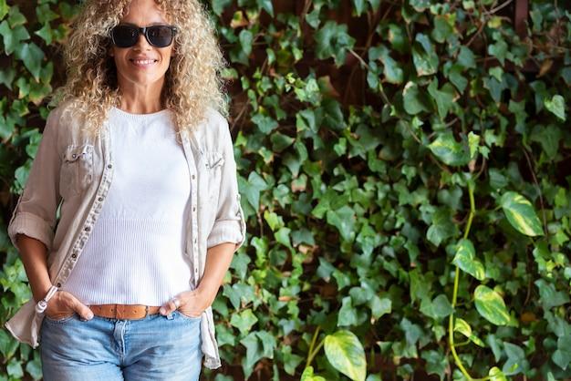 ポケットに手を入れて、新鮮な緑の葉の背景の前に屋外に立っている巻き毛とサングラスを持つ美しい流行に敏感な女性。ツタの葉の背景の前にスタイリッシュな女性の肖像画