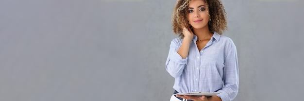 아름다운 히스패닉 비즈니스 여성은 회색 벽의 배경에 대해 클립보드를 손에 들고 있습니다. 비즈니스 컨설턴트 서비스 개념
