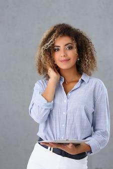 Красивая латиноамериканская деловая женщина держит в руках буфер обмена на серой стене