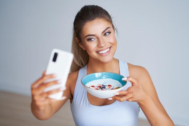 ヨーグルトを食べ、健康的なライフスタイルとダイエットを促進するスマートフォンを保持している美しいヒスパニック系女性
