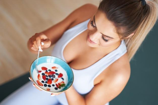 健康的なライフスタイルとダイエットを促進するヨーグルトを食べる美しいヒスパニック系女性