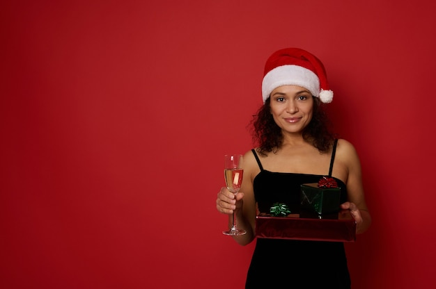 아름다운 히스패닉계 여성은 반짝이는 빨간색 녹색 선물 종이에 싸인 크리스마스 선물 상자와 스파클링 와인이 든 샴페인 플루트, 빨간색 배경에 포즈, 카메라를 보며 귀여운 미소를 짓고 있습니다. 복사 공간