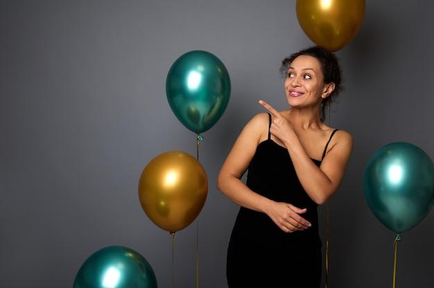 검은 벨벳 이브닝 드레스를 입은 아름다운 히스패닉 여성, 공기 풍선과 함께 회색 배경에 복사 공간에 검지 손가락으로 가리키는 쪽을 바라보는 미소. 생일, 크리스마스, 새해 개념입니다.