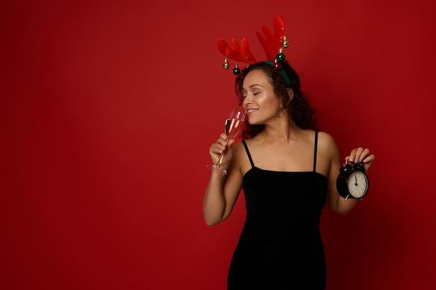 사슴뿔 고리와 검은 벨벳 드레스를 입은 아름다운 히스패닉 여성은 알람 시계를 들고 빨간색 배경에 격리된 샴페인과 함께 플루트에서 스파클링 와인을 마시고 있습니다. 크리스마스 컨셉