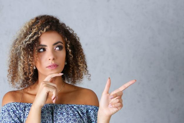 Красивая латиноамериканская женщина с задумчивым лицом указывает жестом пальца в сторону