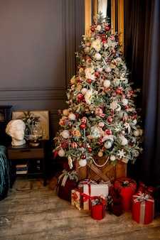 Beautiful holdiay decorated room with christmas tree with presents under it. new year decorated classic home interior. cozy room ready to celebrate christmas. christmas interior design, xmas tree