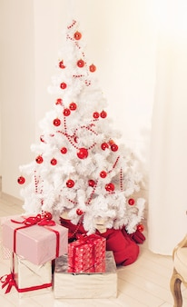 Beautiful holdiay decorated room with white christmas tree with presents under it.