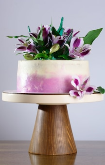 A beautiful holiday cake decorated with fresh flowers.