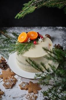 みかんで飾られたクリスマスの美しいホリデーケーキ新鮮なベリーの雪片